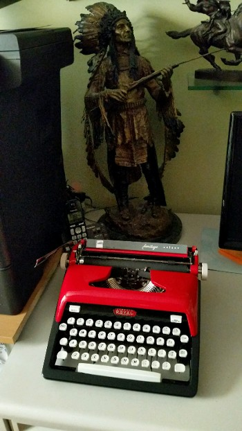 Black and Red Typewriter Near an Indian Statue